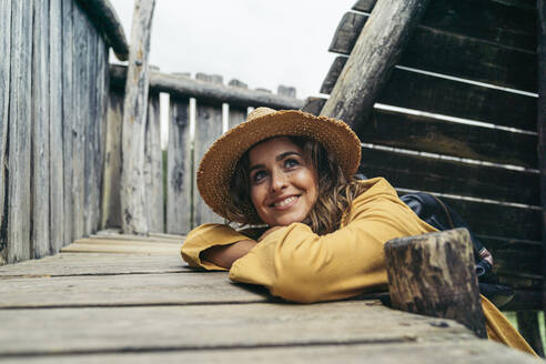 Young smiling woman wearing yellow coat and hat on top of wood stairs, looking sideways - MTBF00003