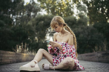 Young woman wearing summer dress with floral design sitting on boardwalk  looking at cell phone - MTBF00021