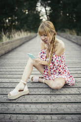 Portrait of surprised young woman  sitting on boardwalk looking at smartphone - MTBF00024