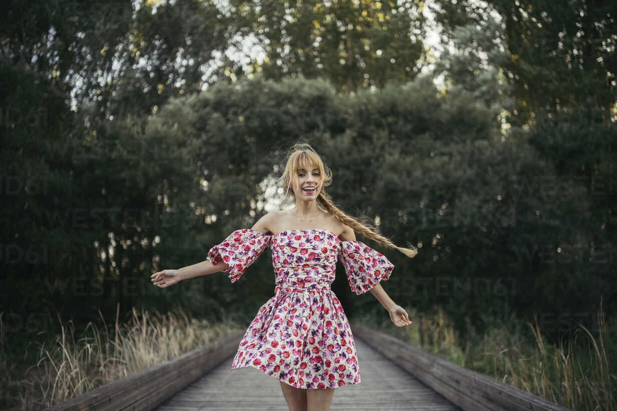 Portrait of happy young woman wearing summer dress with floral design dancing on boardwalk - MTBF00027 - Mikel Taboada/Westend61