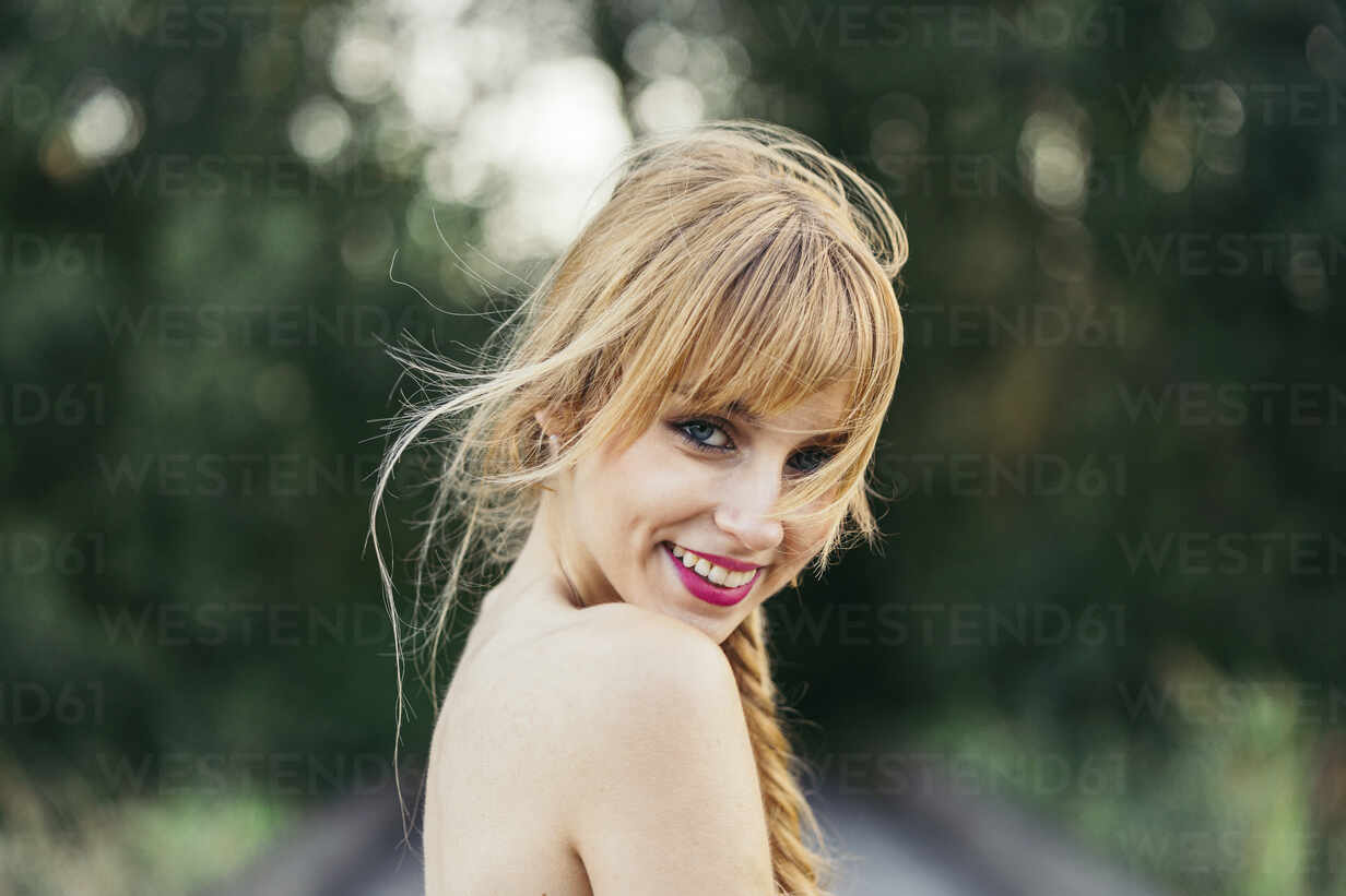 Portrait of smiling blond young woman in nature - MTBF00033 - Mikel Taboada/Westend61