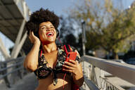 Laughing Afro-American woman with headphones and smartphone listening music - ERRF01725