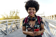 Smiling Afro-American woman with headphones and smartphone - ERRF01728