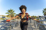 Female Afro-American with headphones and smartphone listening music - ERRF01746