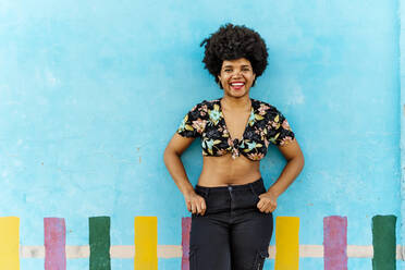 Smiling Afro-American woman in front of a blue wall looking at camera - ERRF01764