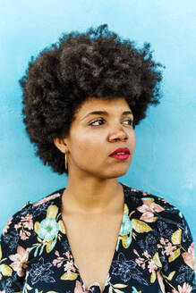 Portrait of female Afro-American woman, blue wall in the background - ERRF01770