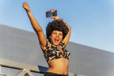 Smiling Afro-American woman with red smartphone - ERRF01779