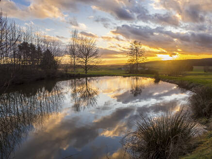 Germany, Bavaria, Clouds reflecting on surface of shiny pond in Upper Palatinate Forest at sunset - HUSF00083
