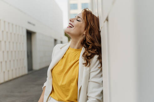 Beautiful businesswoman in white pant suit, leaning on wall, laughing - ERRF01821