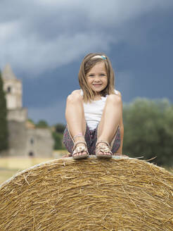 Portrait of smiling little girl sitting on hay bale - XCF00292