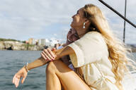 Two beautiful women enjoying a summer day on a sailboat - MGOF04148