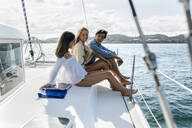 Three young friends enjoying a summer day on a sailboat - MGOF04151