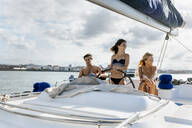 Three young friends enjoying a summer day on a sailboat - MGOF04157