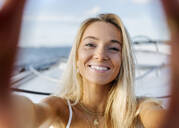 Young beautiful woman taking a selfie on a sailboat - MGOF04187