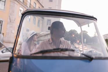 Tuk tuk driver providing tour of the city to a tourist, Lisbon, Portugal - AHSF00989