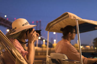 Tourist taking a photo with a camera in a tuk tuk at night, Lisbon, Portugal - AHSF00992