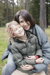 Mother hugging smiling son in a park - EYAF00614