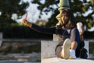 Smiling businesswoman sitting outdoors making a selfie - GIOF07301