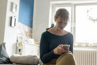 Smiling woman sitting in the living room using smartphone - KNSF06825