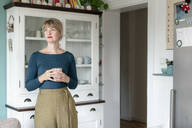 Portrait of woman standing in the kitchen with cup of coffee looking at distance - KNSF06828