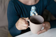 Woman's hands holding mug with little robot - KNSF06837