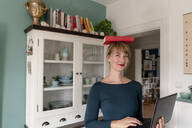 Portrait of smiling woman standing with laptop in the kitchen balancing book on her head - KNSF06843