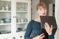 Portrait of pensive woman standing with laptop in the kitchen looking at distance - KNSF06846
