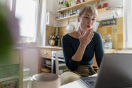 Portrait of young woman using laptop in the kitchen, blowing a kiss - KNSF06852