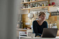 Portrait of smiling woman sitting in the kitchen using laptop - KNSF06858