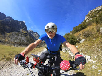 Senior man with his electric mountain bike riding through the Alps - LAF02383