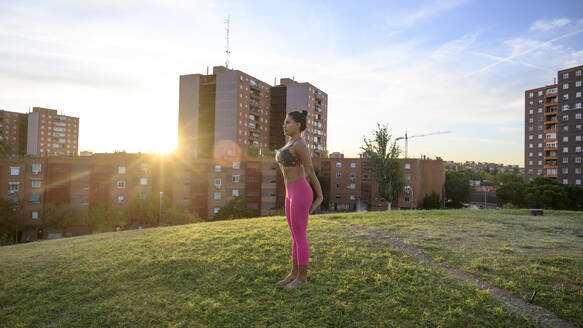 Woman performing abdominal hypopressive exercises outdoors - OCMF00821