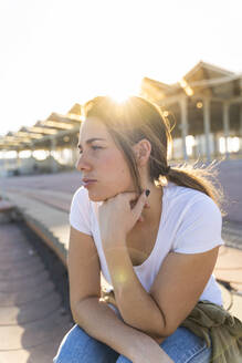 Portrait of young woman at backlight looking at distance - AFVF04078