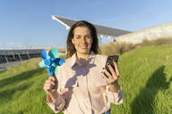 Portrait of smiling young woman with pinwheel and mobile phone - AFVF04090