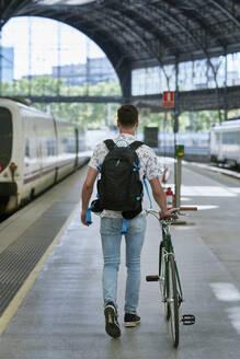 Man pushing bicycle through a station - JNDF00131
