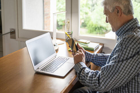 Senior man sitting in front of laptop using smartphone at home - AFVF04107