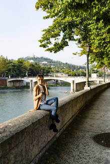 Woman with earphones sitting at riverside using smartphone - GIOF07313
