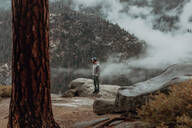 Hiker enjoying view of fog covering valley, Yosemite National Park, California, United States - ISF22314
