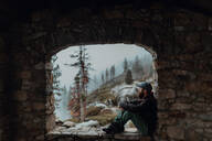 Hiker enjoying view of misty valley on ledge, Yosemite National Park, California, United States - ISF22317