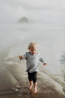 Toddler walking on beach, Morro Bay, California, United States - ISF22341