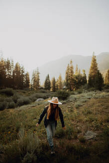 Young woman in stetson walking in rural valley, Mineral King, California, USA - ISF22359