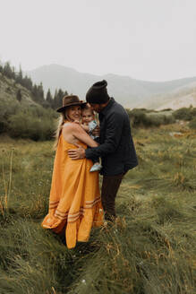 Pregnant mid adult couple hugging toddler daughter in rural valley, portrait, Mineral King, California, USA - ISF22401