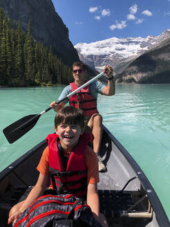 Man and boy canoeing on Lake Louise, Alberta, Canada on summer day. - CAVF65685