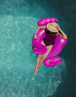 Top view of woman floating on inflatable pink flamingo in a pool. - CAVF65691