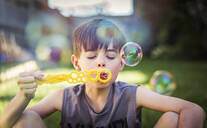 Young boy blowing bubbles outdoors on a summer day. - CAVF65694