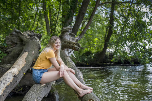 Smiling woman sitting on a tree trunk at lakeshore - BFRF02104