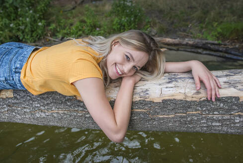 Smiling woman laying on a tree trunk at lakeshore - BFRF02107