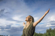 Smiling woman standing with outstretched arms outdoors - BFRF02131