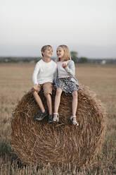 Two kids sitting on the haystack - EYAF00626