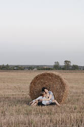 Woman with two kids sitting near a haystack on a stubble field - EYAF00629