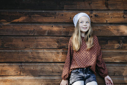 Smiling girl standing in front of a wooden wall outdoors - HMEF00652